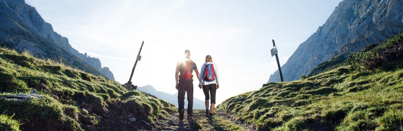Ein Wanderweg im Mittelpunkt des Bildes. Dazu links und rechts Berge und grüne Fläche. Auf dem Wanderweg läuft ein Paar mit Rucksäcken Hand in Hand der Sonne entgegen.