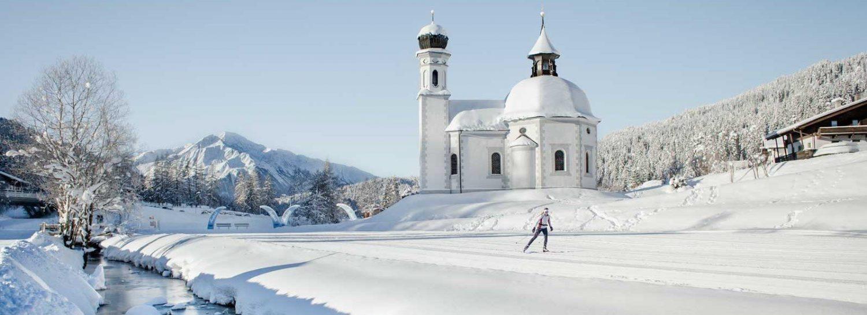 Eine Winterlandschaft mit Bergen und Wäldern im Hintergrund. Im Vordergrund ist ein Langläufer vor einer Kirche. Links ist ein Bach und die gesamte Landschaft ist verschneit.
