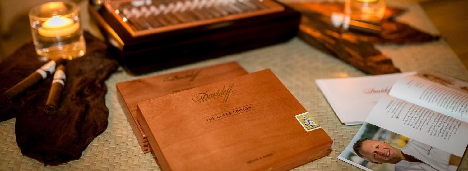 Auf einem Tisch liegen cremefarbene Untersetzer. Darauf sind zwei brennende Kerzen und drei Zigarren-Schachteln. Die eine Zigarrenschachtel ist geöffnet. Die zwei anderen Schachteln stehen geschlossen im Vordergrund des Bildes. Zwei Zigarren liegen einzeln links im Bild. Rechts im Bild sind Prospekte von Davidoff.