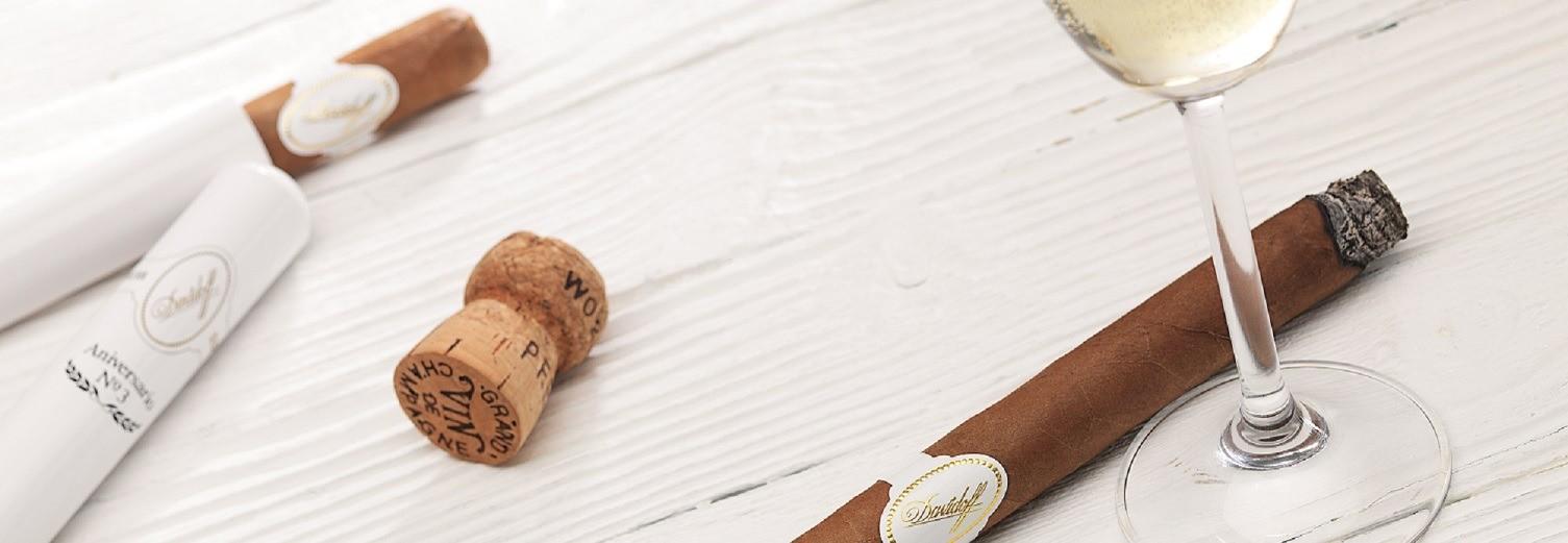 Ein heller Holzhintergrund mit Zigarren von Davidoff. Die Zigarren sind braun und in einer weißen Verpackung. Eine ist bereits benutzt worden und liegt neben einem Glas Sekt. Der Korken der Sektflasche liegt ebenfalls auf dem Tisch.