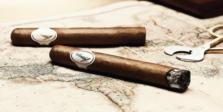Zwei braune Zigarren, die das Siegel von Davidoff tragen, liegen auf einer alten Weltkarte. Eine von den Zigarren ist bereits benutzt worden.
