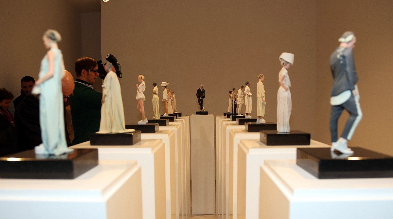 15 helle 3D-Figuren stehen auf Podesten aufgereiht. In der linken Reihe stehen sieben Figuren, in der rechten Reihe ebenfalls sieben Figuren. Zwischen diesen beiden Reihen steht ganz vorne eine 3D-Figur von Michael Michalsky. Neben der linken Reihe stehen einige Fotografen und Besucher.