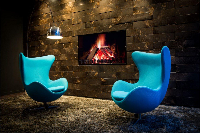 Zwei blaue Sessel vor einer dunklen Steinwand mit eingebautem Kamin. Unter den stühlen ist ein brauner flauschiger Teppich. Von der Decke hängt eine silberne Lampe.