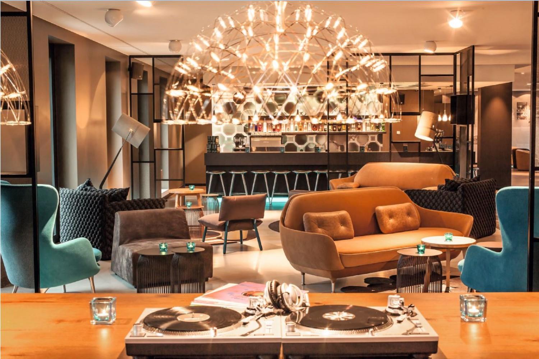 Die Lobby beziehungsweise der Eingangsbereich eines Hotels von Motel One. Braune Sofas und blaue Sessel sowie kleine braune Beistelltische mit blauen Kerzen stehen in der Lobby. Im Hintergrund ist eine Bar mit mehreren Barhockern zu sehen. Viele helle Lampen bringen den Raum zum Strahlen. Im Vordergrund ist ein kleines DJ-Pult.