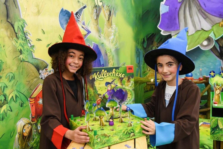 """Ein grün-blauer Hintergrund, der einen Hexenwald darstellt. Rechts hinten ist ein kleiner Tisch mit mit einer Hexenkugel und einem Hexenbesen. Im Vordergrund sitzen zwei Mädchen, die als Hexen verkleidet sind, an einem Tisch und präsentieren das Spiel """"Kullerhexe"""" von Schmidt Spiele."""