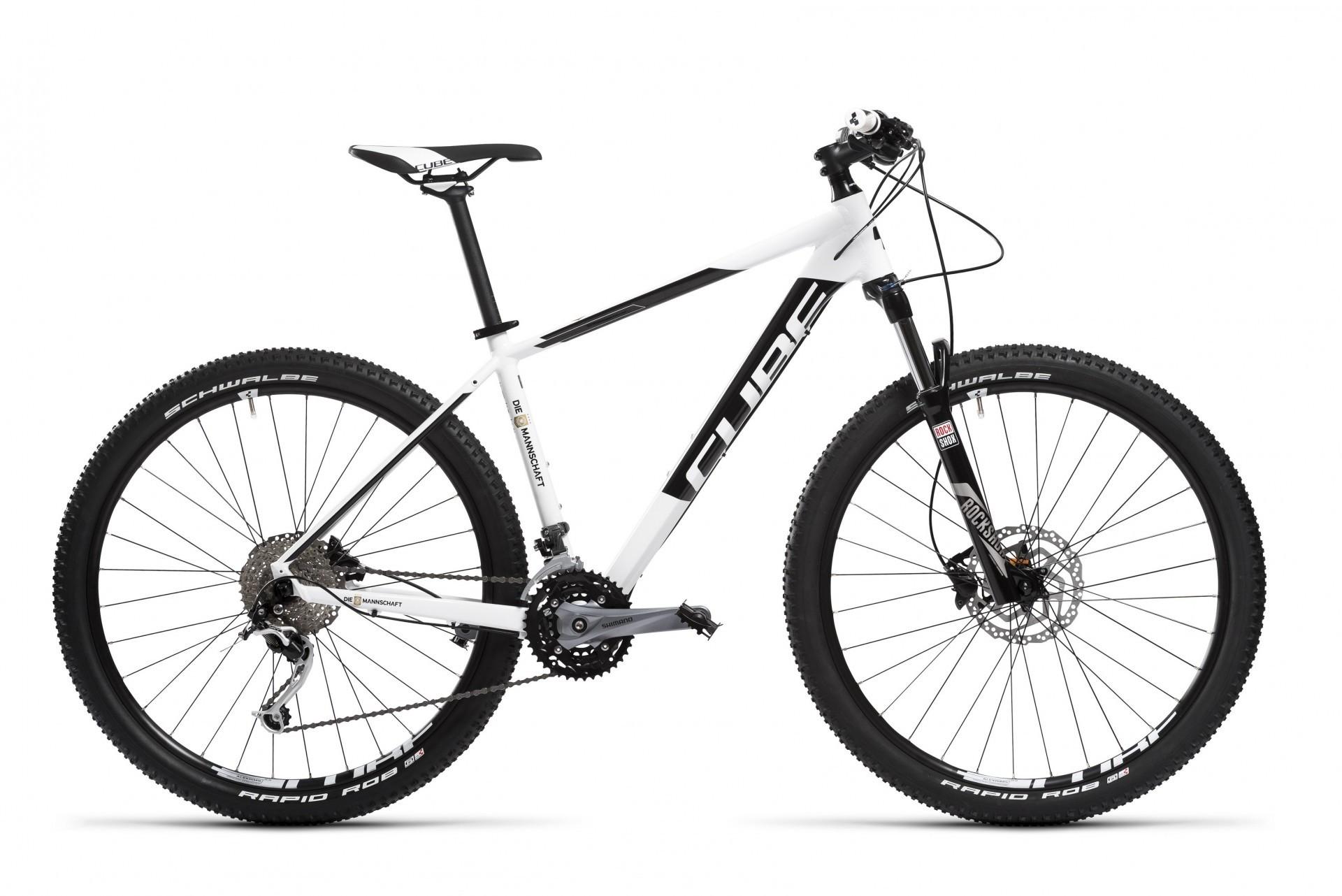 """Ein weißer Hintergrund. Im Vordergrund ist ein weiß-schwarzes Herrenrad mit dem Schriftzug """"CUBE"""". Die Reifen des Fahrrads sind dicker und breiter als normale Fahrradreifen."""