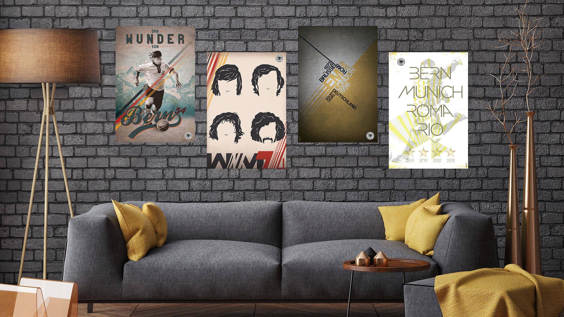 Im Hintergrund ist eine Steinwand. An der Wand befinden sich vier Plakate/Poster des deutschen Fußball Bundes. Außerdem ein graue Couch mit sechs gelben Kissen. Links von dem Sofa steht eine große bräunliche Lampe. Rechts von dem Sofa sind zwei roséfarbene Vasen mit Ästen. Vor dem Sofa steht ein kleiner Beistelltisch und ein grauer Hocker mit einer gelben Decke. Man erkennt deutlich, dass es eine Fotomontage ist.