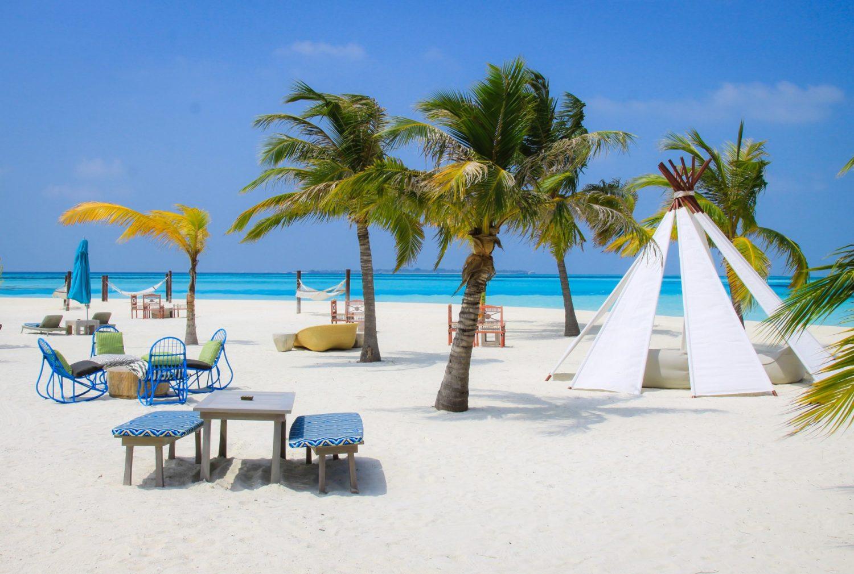 Ein riesiger Strand mit klarem blauen Wasser im Hintergrund. Der Sand im Vordergrund ist sehr hell und es befinden sich Palmen, Tische, Stühle, ein Tipi sowie ein paar Hängematten an dem Strand.