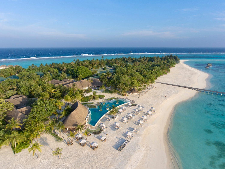 Ein Strand ist links und rechts umgeben von klarem blauem Wasser. Im hinteren Bereich des Strandes sind Palmen und andere grüne Pflanzen. Mehrere Hütten und Sitzmöglichkeiten befinden sich auf dem vorderen Teil des Strandes. In der Mitte des Strandes ist ein Pool und von dem Strand führt ein langer schmaler Steg in das Wasser.
