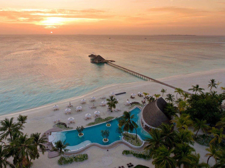 Ein Strand der von klarem Wasser umgeben ist. An dem Strand sind mehrere Hütten und Sitzmöglichkeiten sowie Palmen und andere grüne Pflanzen. In der Mitte ist ein Pool. Ein langer schmaler Steg führt in das Meer hinein. Am Ende des Stegs ist eine große Hütte. Es ist Abend und es dämmert - die Sonne geht unter.