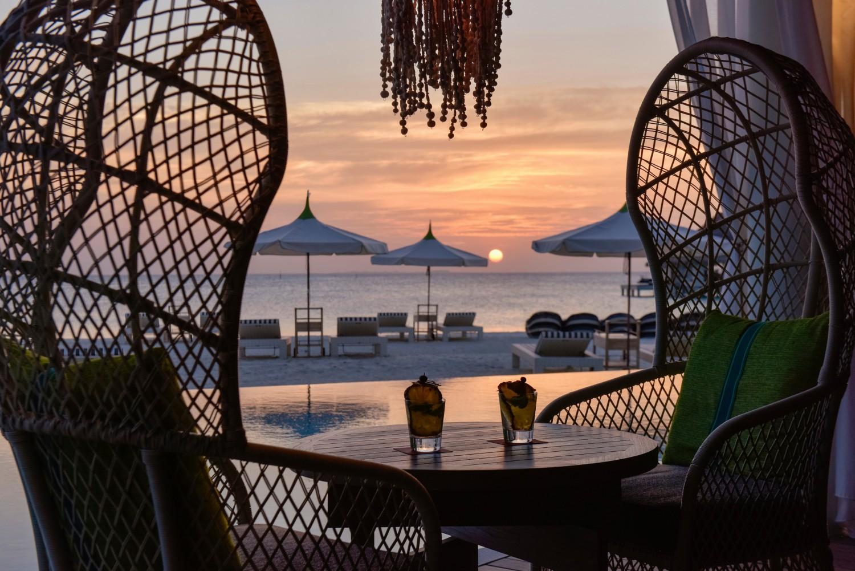 Im Hintergrund ist die untergehende Sonne und der aufgehende Monde. Vorne am Strand sind Sitz- und Liegemöglichkeiten. Im Vordergrund sind zwei große Strandstühle mit Kissen und ein Tisch mit zwei Cocktails. Über dem Tisch hängen mehrere kleine Ketten von der Decke.