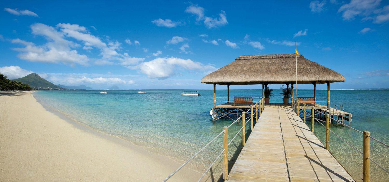 Ein Strand mit klarem blauen Wasser im Hintergrund. Der Sand im Vordergrund ist sehr hell und es führt ein Steg in das Wasser hinein. Auf dem Wasser sind ein paar Boote und im Hintergrund ein paar Berge.