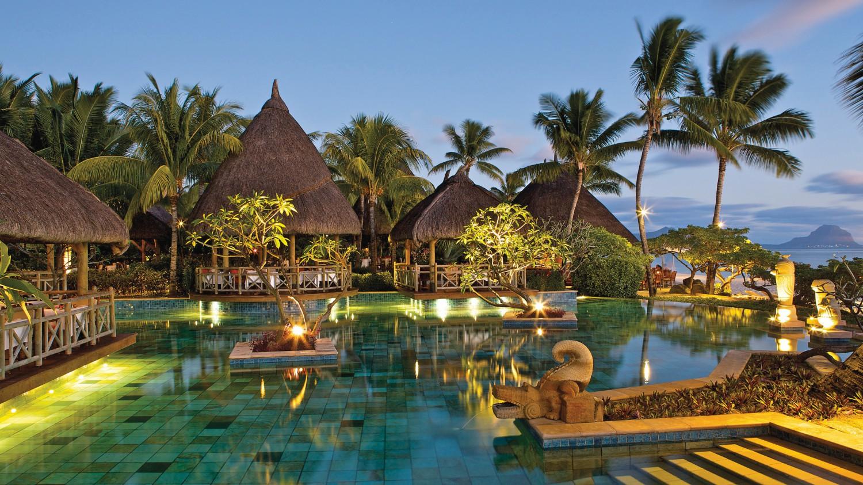 Eine Hotelanlage mit sechs kleinen Hütten, in denen man sich entspannen und gemeinsam essen kann. Im Zentrum der Hütten ist ein riesiger beleuchteter Pool. Es ist abend, es dämmert und es sich viele Palmen und andere Pflanzen um die Anlage gepflanzt.