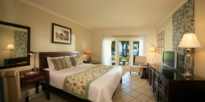 Ein großes geräumiges Hotelzimmer mit hellen Wänden. Im Hintergrund ist die Terassentür, durch die man das Meer, die Palmen und die Terasse sieht. Die Möbel sind alle in dunklem Holz gehalten. Teil der Möbel sind ein großes Doppelbett, ein Bild über dem bett, ein Schreibtisch, ein Spiegel über dem Schreibtisch, ein Nachttisch, zwei Sessel, eine TV-Kommode, ein Beistelltisch und ein Schreibtischstuhl. Vier Lampen befinden sich in dem Zimmer und es werden grüne Akzente in der Bettwäsche, den Polstern und den Wänden gesetzt. Auf der TV-Kommode befindet sich ein silber-grauer Fernseher.